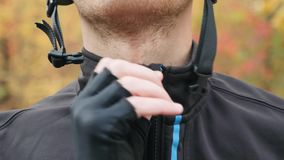 Professional male cyclist closing zipper on jacket and helmet clasp before outdoors workout on bike in autumn forest. Extra close. Up front view of young stock video