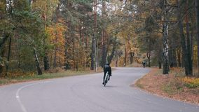 Professional male cyclist hard training on road bike in fall city park. Young attractive triathlete in helmet intensive pedaling o. N bicycle in autumn forest stock video