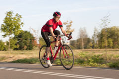 Professional Male Cyclist in Racing Outfit. Cycling Concepts. Professional Male Cyclist in Racing Outfit During a Ride on Bike Outdoors. Panning Technique Used Royalty Free Stock Image