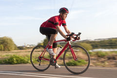 Professional Male Cyclist in Racing Outfit During a Ride on Bike Outdoors. Cycling Concepts. Professional Male Cyclist in Racing Outfit During a Ride on Bike royalty free stock photography