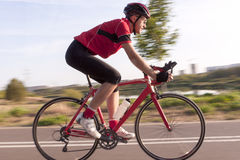 Professional Male Cyclist in Racing Outfit During a Ride on Bike Outdoors. Sport and Cycling Concepts. Professional Male Cyclist in Racing Outfit During a Ride Royalty Free Stock Image