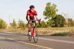 Professional Male Cyclist in Racing Outfit During a Ride Stock Photos