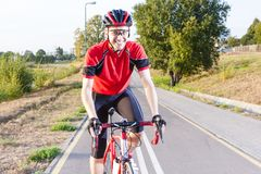 Professional Male Cyclist Riding Road Bike. Equipped with Summer Outfit. Professional Male Cyclist Riding Road Bike. Equipped with Summer Bike Outfit.Outdoor Stock Photo