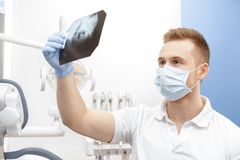 Professional male dentist examining teeth x-ray. Modern technologies. Professional dentist examining dental x-ray of jaw and teeth at his office doctor stock photos