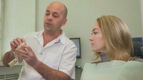 Professional male dentist orthodontist of his female client. Professional look. Professional male dentist orthodontist checking teeth of his female client. The stock video