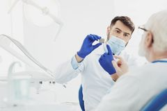Professional male dentist showing problem royalty free stock images