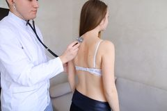 Experienced male therapist diagnoses young woman who came to rec. Professional male doctor advises and conducts general examination, applies stethoscope to back Stock Images