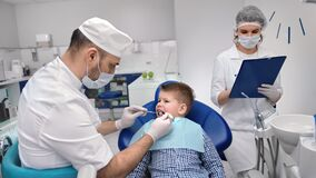 Male doctor and nurse assistant examining mouth cavity of kid. Medium shot on RED camera