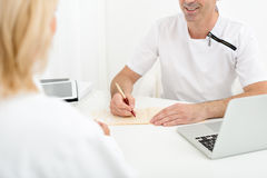 Professional male doctor writing satisfactory diagnosis royalty free stock photos