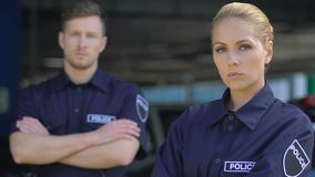 Professional male and female cops looking on camera, responsible police service stock video footage