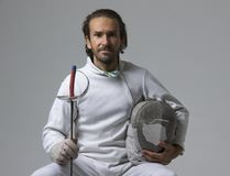 Professional male fencer holding mask and sabre while sitting on chair Royalty Free Stock Photo