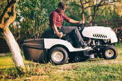 Professional male gardner using lawn mower for cutting grass in home garden. Professional male landscaper using lawn mower for cutting grass in home garden Royalty Free Stock Photos