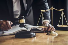 Professional Male lawyer or judge working with contract papers, documents and gavel and Scales of justice on table in courtroom, royalty free stock photos