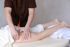 Professional male masseur kneads legs of girl to patient, who li Royalty Free Stock Images