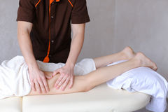 Professional male masseur kneads legs of girl to patient, who li Royalty Free Stock Photography