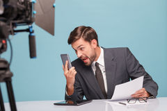 Professional male newscaster is foaming at the Stock Photos