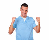 Professional male nurse celebrating his victory. Portrait of professional male nurse on blue uniform celebrating his victory while standing and smiling at you on Stock Photography