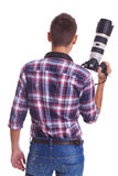 Professional male photographer holding his camera. Back view of a professional male photographer holding his big camera . isolated on white background royalty free stock images