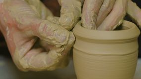 Professional male potter making ceramics in workshop. Professional male potter working in workshop, studio. Close up shot of potter`s hands. Handmade, small