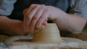 Professional male potter working with clay on potter`s wheel. In workshop, studio. Handmade, art and handicraft concept stock footage