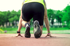 Professional male runner taking ready to start position. Young male runner taking ready to start position Stock Image