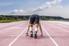 Professional male runner taking ready to start position. Young male runner taking ready to start position Royalty Free Stock Images