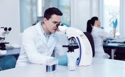 Professional male scientist doing a research. Modern laboratory. Professional handsome male scientist sitting at the table and looking into the microscope while Stock Images
