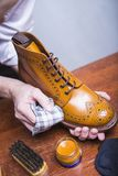 Professional Male Shoe Cleaner Using Cloth. Footwear Cleaning Ideas. Professional Male Shoe Cleaner Using Cloth and Brush For Tan Derby Boots. Working in Stock Photography