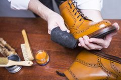 Professional Male Shoes Cleaner Polishing Male Tan Brogue Derby Boots. Footwear Ideas. Professional Male Shoes Cleaner Polishing Male Tan Brogue Derby Boots with Stock Image