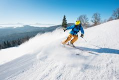 Skier riding in the mountains on a sunny winter day. Professional male skier riding the slope on a beautiful winter day copyspace ski resort travelling tourism Stock Photos