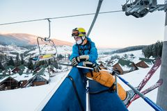 Skier guy sitting at ski chair lift in beautiful day and turns back. Close-up. Concept of skiing. Stock Photography