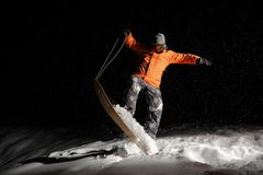 Male snowboarder in orange sportswear balancing on snow at night. Professional male snowboarder dressed in orange sportswear and protective glasses balancing on royalty free stock photo