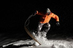 Professional male snowboarder in orange sportswear jumping on snow at night. Professional male snowboarder dressed in orange sportswear and protective glasses Stock Image