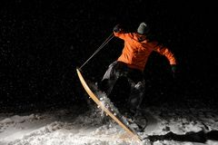 Professional male snowboarder jumping on snow at night. Professional male snowboarder dressed in a sportswear and protective glasses jumping on snow at night Stock Photo