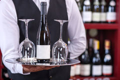 Professional male sommelier is serving alcohol. Close up of hands of wine waiter. He is holding a tray with bottle of wine and two glasses. The man is standing Stock Image