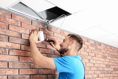 Male technician installing alarm system indoors royalty free stock photo