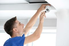 Technician installing CCTV camera on ceiling indoors. Professional male technician installing CCTV camera on ceiling indoors Stock Photos