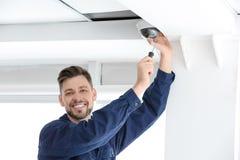 Technician installing CCTV camera on ceiling indoors. Professional male technician installing CCTV camera on ceiling indoors Royalty Free Stock Photography