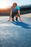 Professional male track athlete in starting blocks stock photos