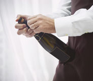Professional male waiter in uniform opening bottle of champagne Royalty Free Stock Photos