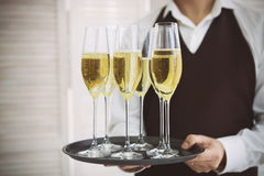 Professional male waiter in uniform serving champagne. DOF Stock Photos