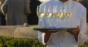 Professional male waiter in uniform serving champagne. Dri Royalty Free Stock Photography