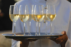 Professional male waiter in uniform serving champagne. Dri Royalty Free Stock Photo