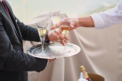 Professional male waiter in uniform serving champagne. Woman taking one glass of champagne. DOF. Natural light. Photo in motion royalty free stock image