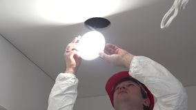 Professional male worker install energy saving led light into ceiling hole. Handheld steadycam flycam movement shot. 4K UHD stock video footage