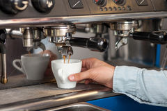Professional male worker is making espresso in. Close up of hand of barista brewing coffee using coffee machine. The man is standing and holding a white cup Royalty Free Stock Photo