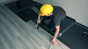 Professional male worker with yellow hard hat installing floor boards stock footage