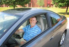 Professional Man Driver. A professional male driving a silver sports car Royalty Free Stock Photography