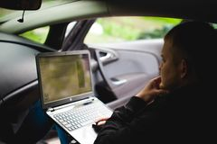 Professional man with a laptop in car tunes tuning control system, updating software, gaining access through to computer Royalty Free Stock Photography