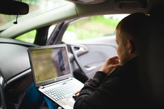 Professional man with a laptop in car tunes tuning control system, updating software, gaining access through to computer Stock Photo